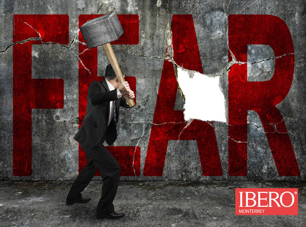 businessman holding sledgehammer hitting red FEAR word on concrete wall