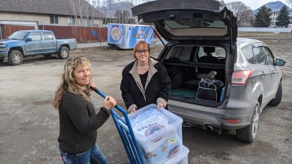 KDLC President Lois Rugg picking up Comfort Cases from IBEW LU 993 Women's Committee member Mollie Routledge at the IBEW LU 993 Center of Excellence for distribution in Kamloops.