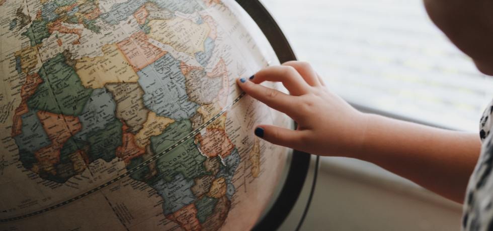 Image of child indicating a country on a globe
