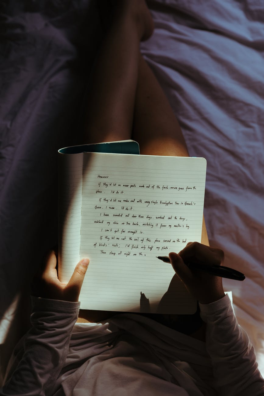 crop lady with pen and notebook on bed at home