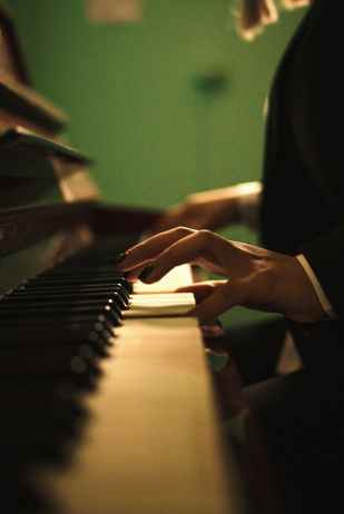 a close up shot of a pianist s hands while playing piano