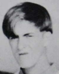 Blurry black and white yearbook photo of a young man with his hair falling over his eyes; he looks like the photo was taken before he got the chance to smile.
