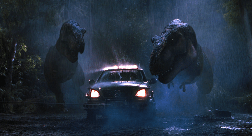Two T-Rexes converge on an SUV during a downpour in THE LOST WORLD: JURASSIC PARK (1997)