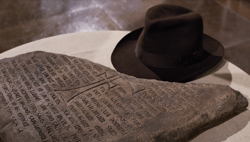 Indy rests his fedora next to half of an ancient Christian artifact in INDIANA JONES AND THE LAST CRUSADE (1989)