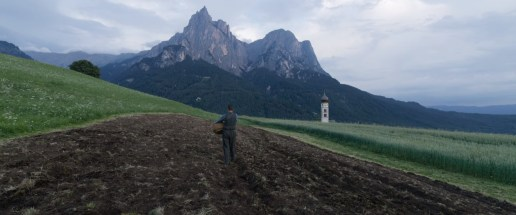 August Diehl stars as real-life Nazi pacifist Franz Jägerstätter, as he plants seeds in a field, in Terrence Malick's A HIDDEN LIFE (2019)