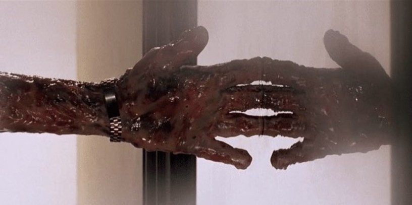 A bloody, ravaged hand attempts to cross a mysterious barrier in THE MATRIX RESURRECTIONS (2021)