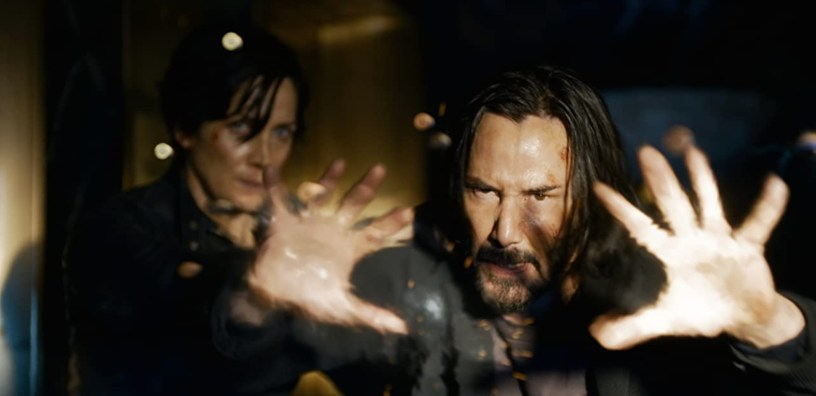 Neo (Keanu Reeves) fights off attackers and bullets with Trinity (Carrie-Anne Moss) in THE MATRIX RESURRECTIONS (2021)