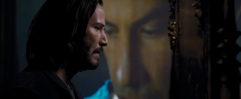 Thomas Anderson (Keanu Reeves) walks past a projected image of himself from the original Matrix film in THE MATRIX RESURRECTIONS (2021)