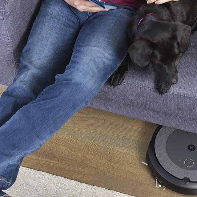 An iRobot Roomba robot vacuums cleaning underneath a couch.