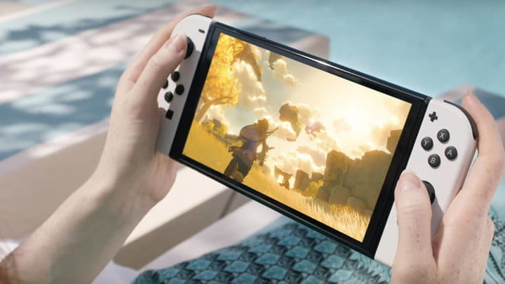 White Nintendo Switch OLED in handheld mode playing Breath of the Wild 2.