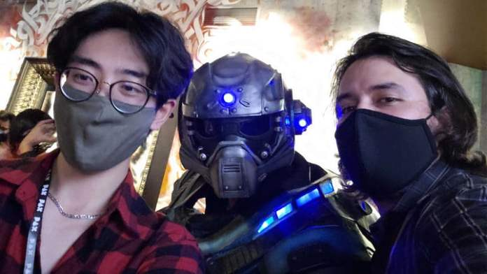 A Gears of War cosplayer taking a picture with two people at PAX West.