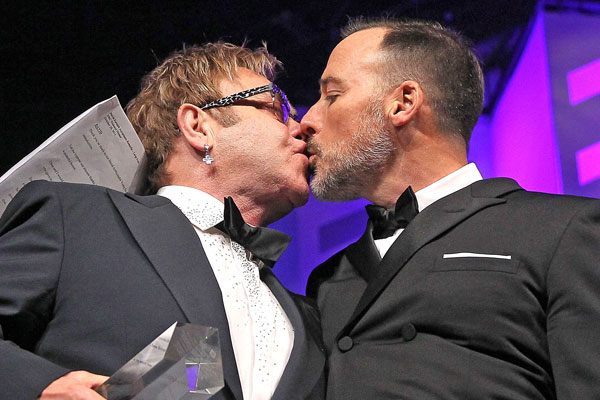 Sir Elton John (L) gives David Furnish a kiss at the 18th Annual HRC National Dinner at The Walter E. Washington Convention Center on October 25, 2014 in Washington, DC. (Photo by Paul Morigi/Getty Images)