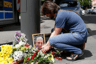 A man lights a candle by a portrait of Pavel Sheremet surrounded with flowers and candles at a place of his death in Kiev, Ukraine, Wednesday, July 20, 2016. A prominent journalist was killed in a car bombing in Ukraine's capital, Kiev, on Wednesday, sending shockwaves through the Ukrainian journalist community that was shaped by the gruesome killing of the publication's founder 16 years ago. (AP Photo/Sergei Chusavkov)
