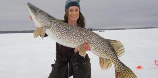 Woman ice fishing holding pike