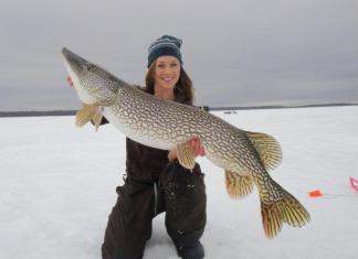 Woman ice fishing holding pike