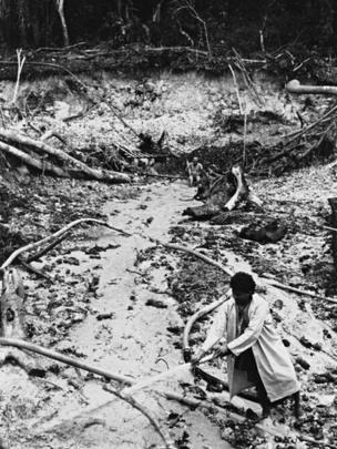 Garimpeiro espalhando a terra com um jato d'água, no garimpo junto à pista do Jeremias, Alto Mucajaí, Terra Indígena Yanomami, Roraima, em 1990.