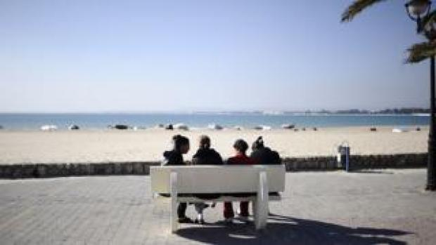 People sit on a bench facing the sea in Hammamet