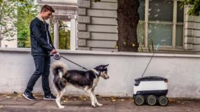 Man walking dog coming face to face with the self-driving robot