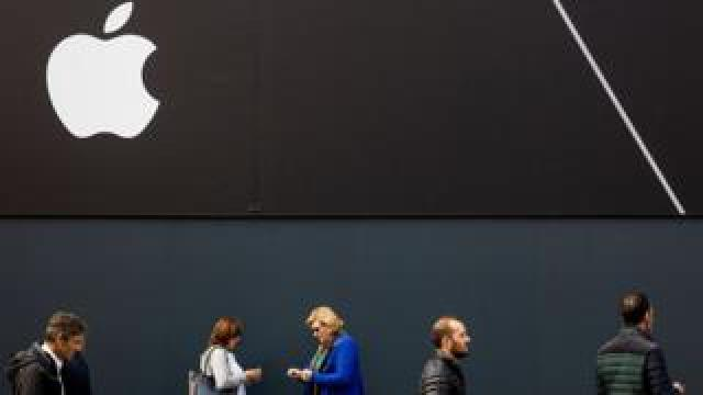 Pedestrians walks past Apple logo