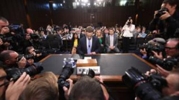 Mark Zuckerberg looks down as he takes his seat in the committee chamber, surrounded by a ring of photographers pressing in around him