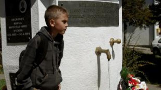 "A boy passes by a memorial for the victims of NATO""s 1999 bombing before a protest described as a parallel parliament, ahead of April 28""s parliament vote to ratify Montenegro""s NATO membership, in the village of Murino, Montenegro"