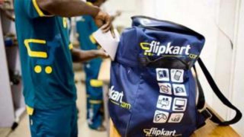 A delivery boy packs his Flipkart bag.