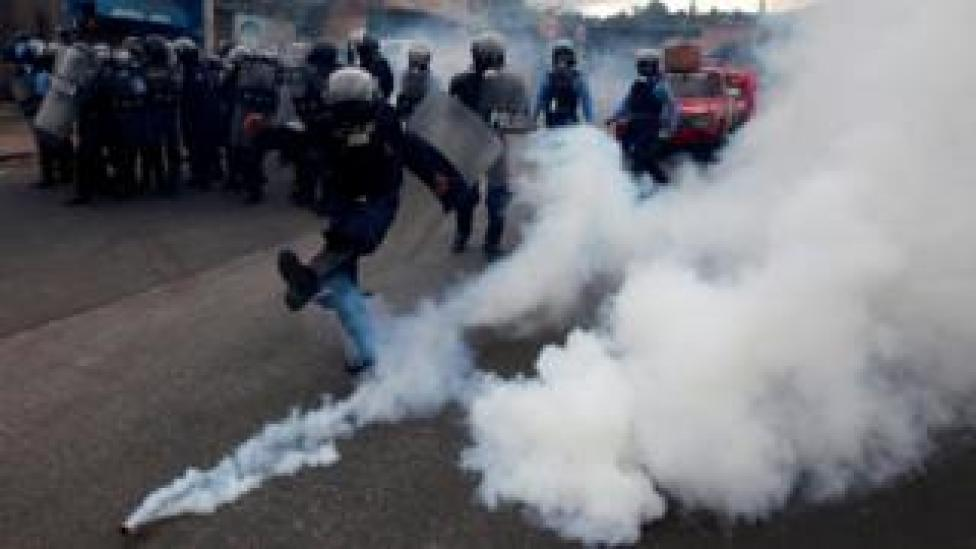 """A riot policeman kicks a tear gas canister to demonstrators, during a protest against the re-election of Honduras"""" President Juan Orlando Hernandez in Tegucigalpa Honduras January 20, 2018."""