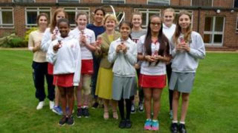 Heather Hanbury with students holding the alarm clock