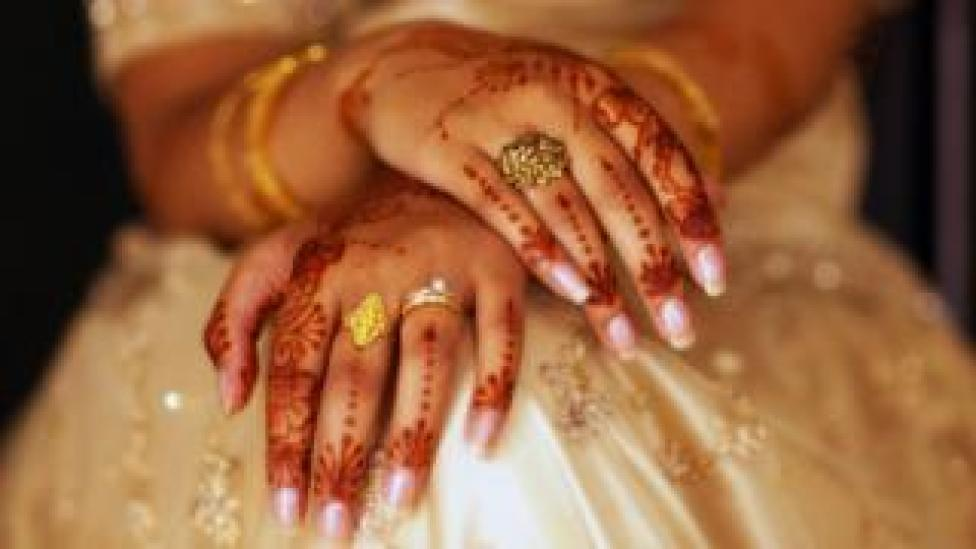 A bride is sitting with her hand covered in henna