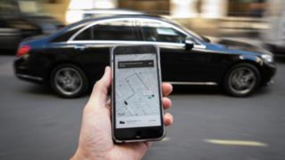 صورة لتطبيق أوبر على هاتف ذكي وخلفه سيارة