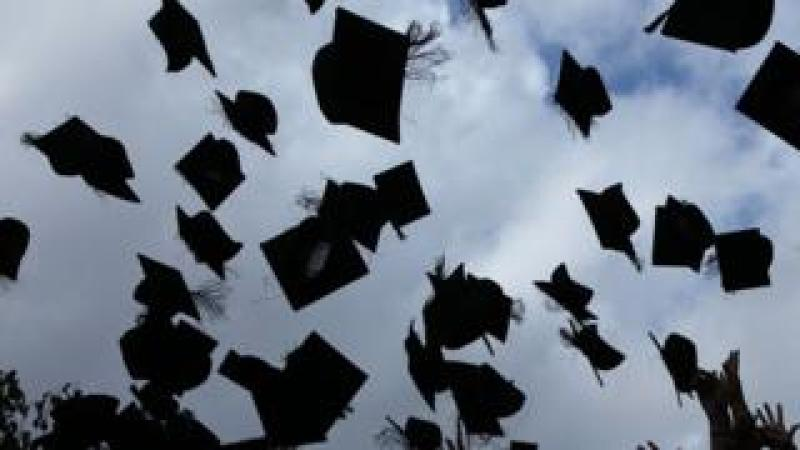 University graduands throw their mortar boards into the air