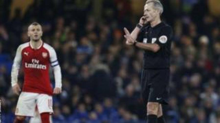Umukinyi wo hagati wa Arsenal Jack Wilshere (mu bubamfu) n'umuhagarikizi w'urwo rukino Martin Atkinson (i buryo)