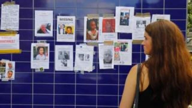 a woman looks at posters of the missing