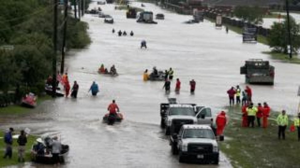 A busy scene shows rescuers and residents in boats and wet gear navigate a flooded street in Houston - in some part people are seen submerged to the waist