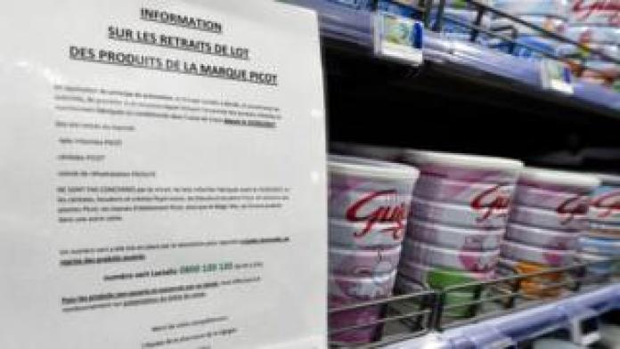 A warning sign is posted in a supermarket in baby milk aisle
