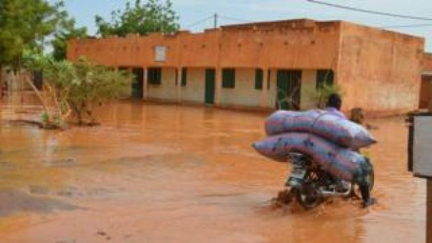 A man rides a motorbike with his belongings in a flooded street of Niamey following heavy rains, on June 15, 2017.
