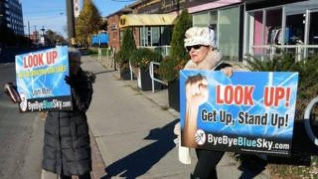 Suzanne Maher with Bye Bye Blue Sky anti-chemtrails placard