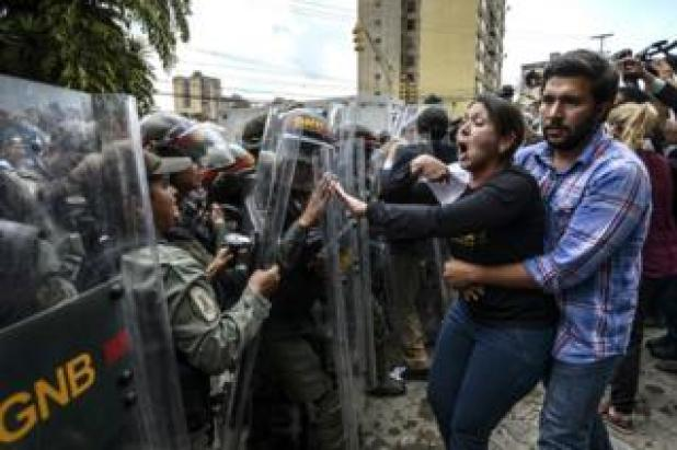 Venezuelan opposition deputy deputy Amelia Belisario (C) argues with National Guard personnel in riot gear during a protest in front of the Supreme Court in Caracas on 30 March 2017