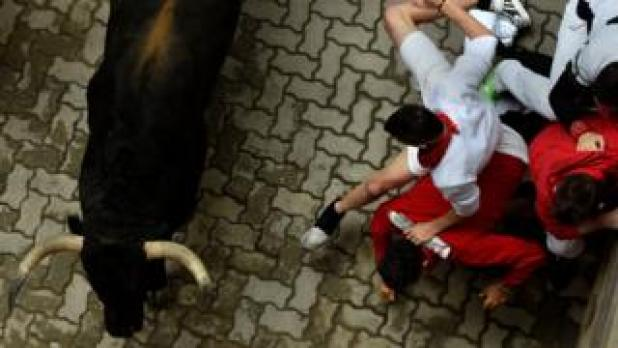 Runners sprint ahead of Fuente Ymbro fighting bulls during the fourth running of the bulls at the San Fermin festival in Pamplona, northern Spain, 10 July