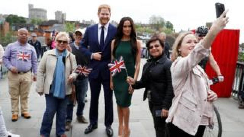 People pose for pictures and selfies with models of Britain's Prince Harry and Meghan Markle ahead of their wedding, in Windsor