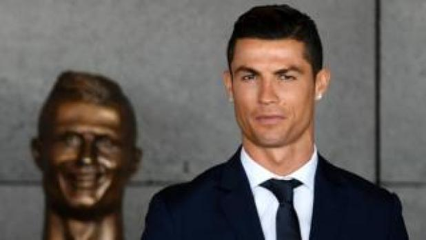 Ronaldo standing by his bust at the unveiling