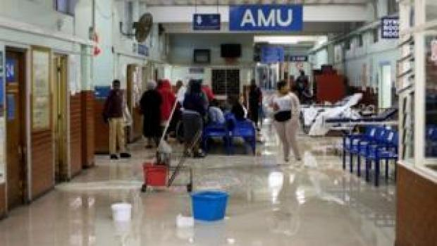 Cleaners mop up water at King Edward VIII Hospital during a storm in Durban, South Africa, 10 October 2017
