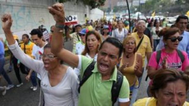 """Opposition supporters shout slogans as they block a highway during a protest against Venezuelan President Nicolas Maduro""""s government in Caracas"""