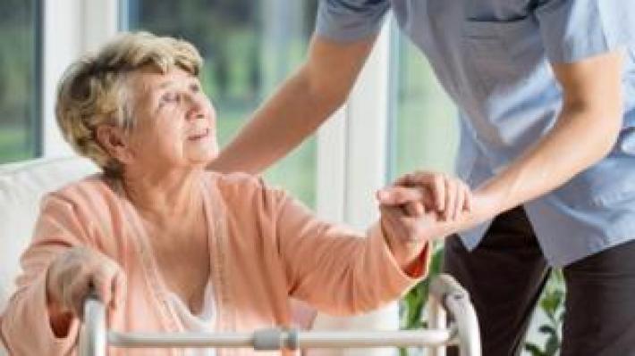 Elderly nursing home resident with carer