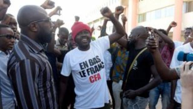 Supporters celebrate in a street of Dakar after the courthouse has decided to release activist Kemi Seba from the Rebeuss jailhouse on August 29, 2017. Kemi Seba was arrested after he burned a 5,000 CFA franc bank note during a meeting on August 19, 2017