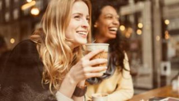 Photo showing two young women laughing and drinking a coffee in a coffee shop.