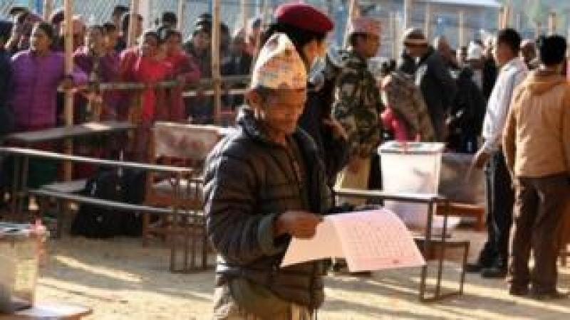A Nepali voter examines a ballot paper before casting his vote at a polling station during the general election at Chautara, Sindhupalchowk district, on November 26, 2017