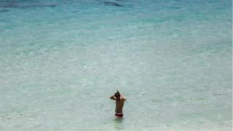 Man wearing a snorkel, standing in the sea on a beach in Phuket