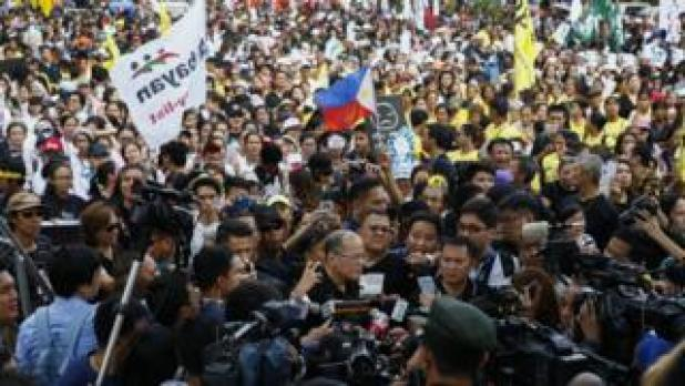 Former Filipino President Benigno Aquino, centre, speaks to media as he joins demonstration to mark 31st anniversary of the People Power Revolution in Quezon City, east of Manila, Philippines. 25 February 2017
