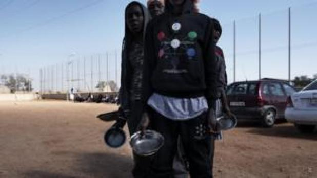 Migrants queue up for food at a detention centre in Libya